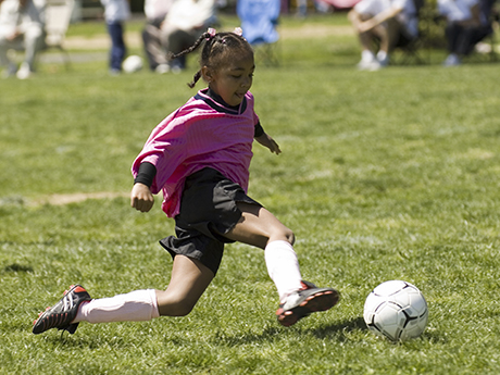 Young African American soccer player kicking the ball.