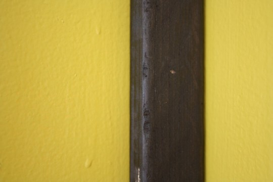 Wee little nail hole. Much better than messing with sloppy, un-stainable wood filler.