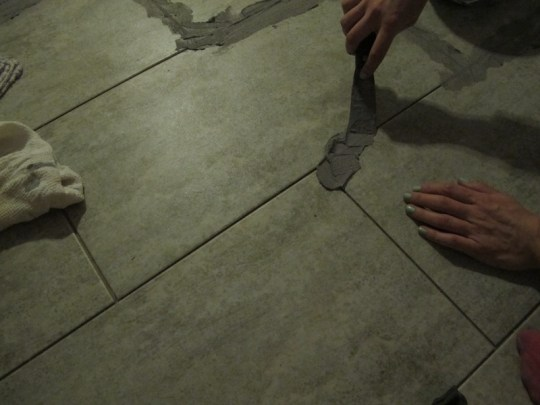 Using a putty knife to gently install grout.