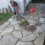 Spreading the sand between flagstones.