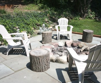 Donna & Pete's pretty fire pit surrounded by flagstone and log tables.