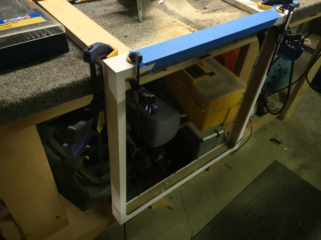Using a router to cut through a IKEA RIBBA frame.