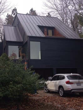 This minimalist, modern home is topped with an industrial standing seam metal roof in the colour Chocolate Brown.