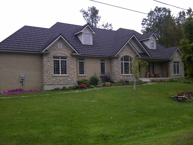 This cottage-like home in Ontario features a mix of fieldstone and brick, topped off with a durable and beautiful Steel Shake roof by Metal Roof Outlet.