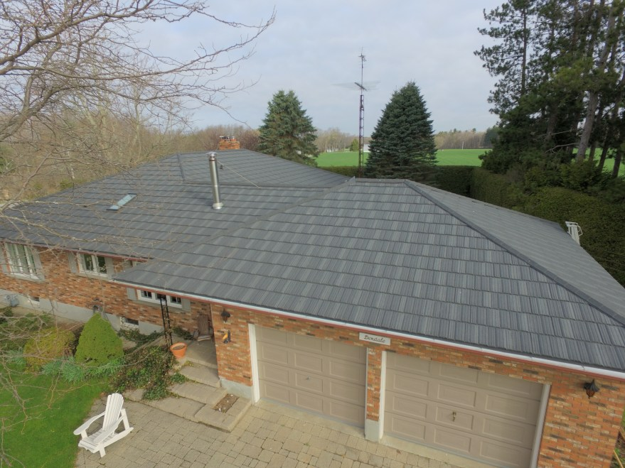 The lovely pumpkin orange of thie brick on this Ontario home needed a subtle shade like the Weathered Wood finish on this steel shake roof.