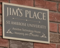Photo shows a plaque on the side of Jims Place at St. Ambrose University honoring Jim O'Rourke