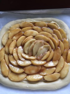 Arrange sauteed apple slices on top of the pastry cream.  Brush the border with heavy cream or egg wash and sprinkle cinnamon sugar all over.