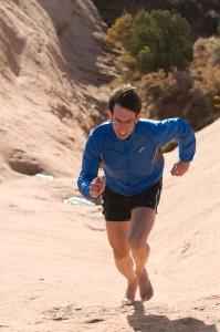 Michael Sanders barefoot running on sandstone slickrock, Moab, Utah.