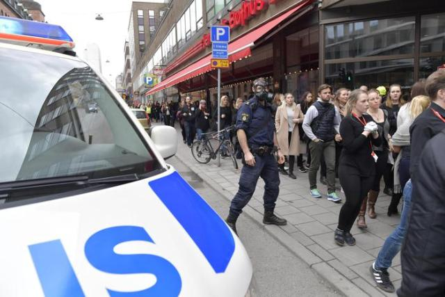 epa05894651 Swedish police officers wearing gas masks watch over people walking at a road after a truck reportedly crashed into a department store in central Stockholm, Sweden, 07 April 2017. A truck has driven into a department store on Drottninggatan street (Queen Street) in central Stockholm, media reported quoting local police. According to initial reports, at least three people were killed and others were injured in the incident, media added. Swedish Prime Minister Stefan Loefven commented that everything indicated the incident as a 'terror attack.'  EPA/JESSICA GOW  SWEDEN OUT