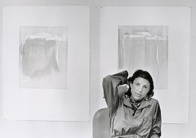 Portrait of Helen Frankenthaler in front of woodblock proofs for Essence Mulberry, 1977