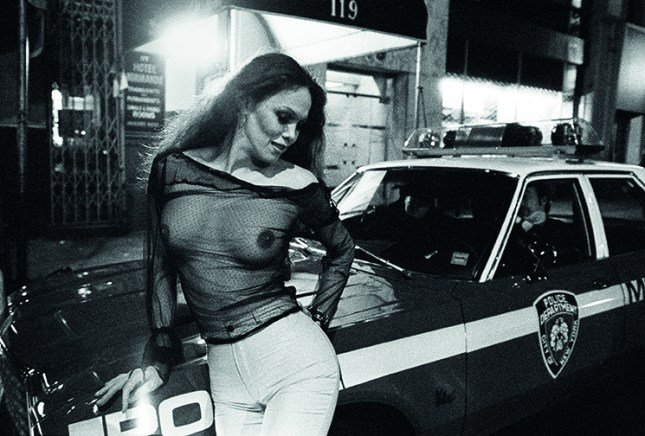 Manhattan, New York City, NY. May, 1980. Prostitute leaning on cop's car on 42nd Street Times Square. Times Square had acquired a reputation as a dangerous neighborhood during the 1980's.  The shabiness of the area, especially due its go-go bars, sex shops, and adult theaters, became an infamous symbol of the city's decline.