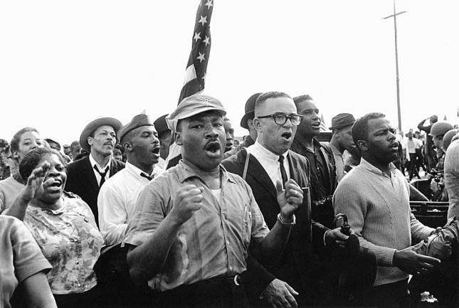Photo: Matt Herron, Selma–Montgomery March, Alabama, 1965: Rev. Martin Luther King leads singing marchers toward Montgomery.