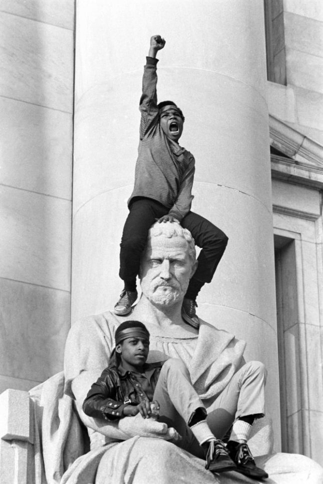 May 1, 1970 - New Haven, Connecticut, USA: Boy gives raised fist salute as he and a friend sit on a statue in front of the New Haven County Courthouse during a demonstration of 15,000 people during the Bobby Seale / Ericka Huggins trial. Bobby Seale, Chairman of the Black Panther Party is on trial along with Ericka Huggins for murder. Both are acquitted.(Stephen Shames/Polaris). ©2016, Stephen Shames from the book Power to the People: The World of the Black Panthers (Abrams). Courtesy Steven Kasher Gallery. Read more at http://www.craveonline.com/art/1124353-power-people-honors-50th-anniversary-black-panther-party#TRxrG83H11cjBkVV.99
