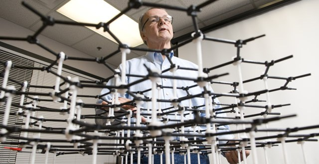 Drzal peers through a model of a carbon molecule. Photo by G.L. Kohuth.