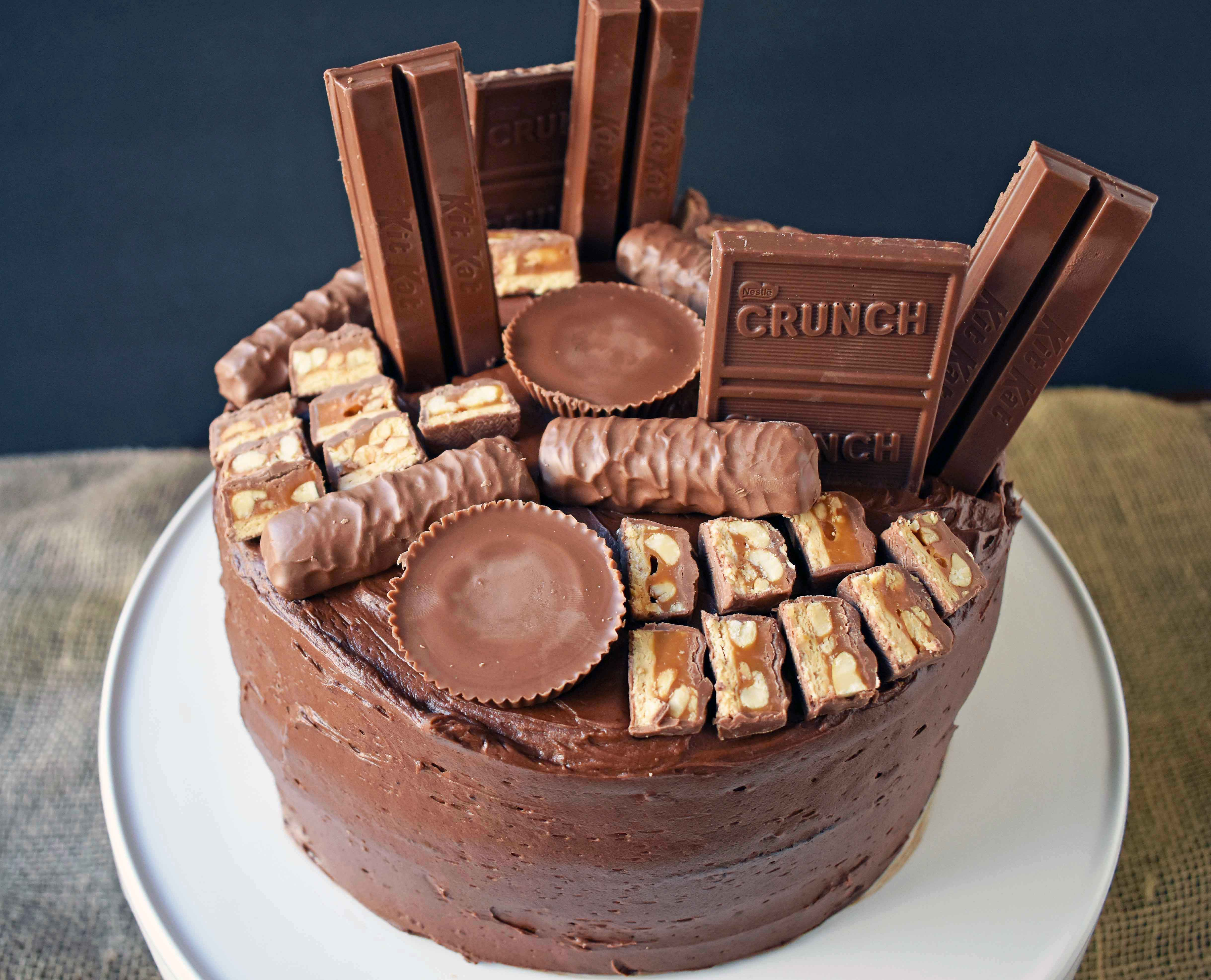 Candy Bar Stash Chocolate Cake by Modern Honey. Perfect chocolate cake topped with chocolate buttercream and the most popular candy bars. It's the ultimate Chocolate Candy Bar Cake.