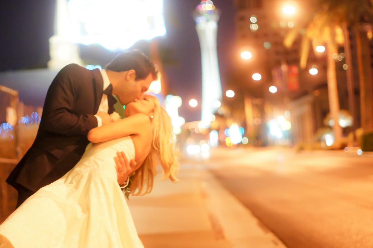 splendid wedding vegas wedding chapels Groom dips his bride for a kiss outside on the Las Vegas Strip in fron of