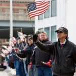 Marine Corps veteran Pat Musco waves an American flag as World War II Army veteran Franklin Johnson's funeral procession passes by him on Maple Street on Saturday.