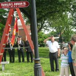 Burgess Robert Burns salutes a new street sign that honors the late Franklin E. Johnson, Sr. as Johnson;s family, looks on at right.