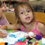 Emily Ambrocio, 4, decorates a mask July 14 as part of a children's program at the Beacon Falls Library.
