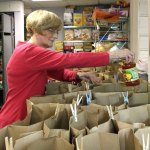 Ellen Rooney, a volunteer at the Ecumenical Food Bank in Naugatuck, bags groceries for low-income individuals and families. The food bank is expecting a lot of customers next week for Thanksgiving.