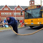 Naugatuck police Officer Derek Poundstone, America's strongest man, pulls a school bus in front of Duggan Elementary School in Waterbury Tuesday. The bus was filled with donated food collected by students and staff from the school. RA ARCHIVE