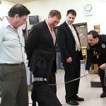 Naugatuck police officer Kevin Zainc, right, demonstrates the ability of K-9 Pete to find drugs planted in the pocket of Dean of Students John Dellacamera, center, flanked by Board of Education member James Scully, left, and Mayor Robert Mezzo during the Board of Education's meeting Dec. 12. The school board teamed up with police to enforce a policy which allows for random drug searches at Naugatuck High School. The first search since the December meeting was performed Thursday. No drugs were found. –FILE PHOTO