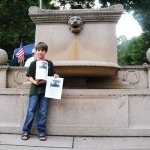 Andrew Treater, 8, of Naugatuck stands by the fountain on the Naugatuck Town Green Tuesday night. For the past two years, Treater has collected donations during summer concerts on the Green to help pay to restore the fountain to its original state. –LUKE MARSHALL