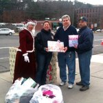Kimberly Tompkins as Mrs. Claus, left, Officer Caroliene O'Bar, Paul Cofield from Beacon Falls Congregational Church, and Lt. Eddie Rodriguez show off toys collected during the Beacon Falls Police Department's annual Stuff a Cruiser on Saturday. The department collected over 200 toys during the event, which were given to St. Michael's Roman Catholic Church and Beacon Falls Congregational Church. –CONTRIBUTED