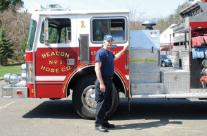 Beacon Falls firefighter and emergency medical technician Kurt Novak stands next to a nearly 25-year-old fire engine in front of Beacon Hose Company No. 1 last April. Novak was hired at the same the department bought the engine. An informational town meeting will be held to discuss how to proceed with buying a new fire truck after the town missed the deadline to apply for a grant. –FILE PHOTO