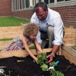 Head Start and School Readiness Program preschooler Jazlyn, 4, of Naugatuck and Naugatuck Valley Savings and Loan President and CEO Bill Calderara plant a cucumber in the Children's Garden at Central Avenue Preschool in Naugatuck July 12. –ELIO GUGLIOTTI