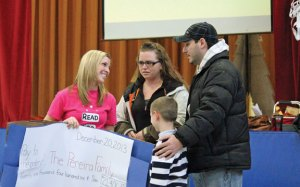 Community School psychologist Laura Naylor, left, presents a check for $21,406.77 to the parents of Brianna Pereira, a fourth grade student at the school in Prospect, Misty and Victor Pereira, as well as Brianna's brother, Camerin Pereira, 7, at an assembly Dec. 20. The money will help with Brianna's medical expenses. Brianna was diagnosed with an anaplastic ependymoma, a brain tumor, in June. The money was raised through a districtwide Read-A-Thon, which was organized by Naylor and Britany Sweet, an intern at Community School. –ELIO GUGLIOTTI