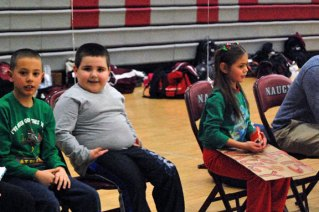 Students from Maple Hill Elementary School in Naugatuck, from left, Hudson Bumbery, Odin Anderson and Leah Quijano watch the Naugatuck High girls basketball game from the bench Dec. 20. The students won a raffle to sit on the sidelines as part of the Maple Hill School Night. The Greyhounds beat Ansonia, 49-27. –KEN MORSE