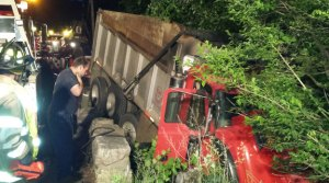 A dump truck is stuck down an embankment along Beacon Valley Road in Beacon Falls early Friday morning. Two tow trucks were called to pull the dump truck out. –CONTRIBUTED