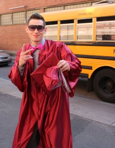 Naugatuck High School Class of 2014 graduate Flamur Nasufi flashes a peace sign as he walks into the Palace Theater in Waterbury for graduation Tuesday.  –LUKE MARSHALL