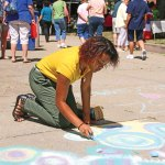 Veronica Rangel of Naugatuck uses chalk to create a colorful design to welcome visitors Aug. 23 to the All Arts Festival on the Naugatuck Green. –LUKE MARSHALL