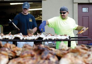 Tim Platt, left, of Bethlehem and John DeCampos Jr. of Naugatuck cook up chickens at the Sao Paio Feast at the Portuguese Club in Naugatuck last year. This year's festival is Labor Day weekend. -RA ARCHIVE