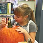 Cailynn Ferrare, 8, of Beacon Falls cuts into her pumpkin during the Beacon Falls Library's pumpkin carving event Oct. 29. –LUKE MARSHALL