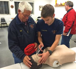 Members of the Volunteer Fire Department of Prospect Bill Seraduck, left, and Patrick Conway III demonstrate how to administer Narcan during a training in August 2014 at the firehouse. –CONTRIBUTED