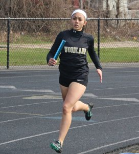 Woodland's Alexa Casimiro in the 4x800 relay on April 12 during a quad-meet with St. Paul, Sacred Heart and Crosby in Beacon Falls. The Hawks have started the season 6-0. –LUKE MARSHALL