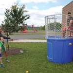 Prospect Elementary School second-grader Alex Donskoy throws a ball to try and dunk Chris McCullen with some coaching from John Butkevicius during Field Day at Prospect Elementary School June 9. –LUKE MARSHALL