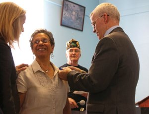 Iluminada Ruiz, center, speaks with state Sen. Joan Hartley, D-Waterbury, left, as Connecticut Department of Veterans' Affairs Commissioner Sean Connolly pins the Connecticut Veterans Wartime Service Medal on her shirt July 28 during a ceremony at the American Legion Post 17 hall in Naugatuck. –LUKE MARSHALL