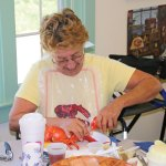 Debbie Mello, of Prospect, pulls the claw off a lobster during a lobster dinner hosted by the Prospect Senior Center Aug. 30. –LUKE MARSHALL