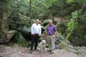 Naugatuck Mayor N. Warren 'Pete' Hess, left, Tax Collector Jim Goggin and Hess' dog, Beau, stop in front of a waterfall along a trail in the Naugatuck State Forest on Aug. 31. The trail, which the borough has been working on since the winter, is part of the 22 kilometer hike that Hess will lead on Sept. 24. –LUKE MARSHALL