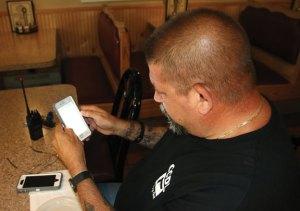 Beacon Falls resident and retired police officer Bill McCasland checks the Nextdoor app on his phone last week. McCasland and his neighbors are using the app as a digital neighborhood watch. –LUKE MARSHALL