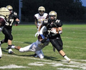 Woodland's Isaac Negron (33) breaks free from a tackle by Sacred Heart-Kaynor Tech's Jordon Wilkins Sept. 23 in Beacon Falls. Sacred Heart/Kaynor Tech won the game, 67-28. –ELIO GUGLIOTTI