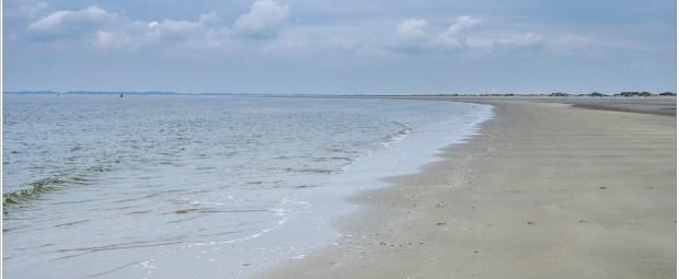 Aan het strand van de Nederlandse kust. Een lege uitgestrekte vlakte met lage duinen aan de horizon. Geen mens is in zicht, maar sporen getuigen van hun aanwezigheid.