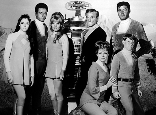Promotional portrait of the cast of the television show, 'Lost in Space,' c. 1966. L-R: Angela Cartwright, Mark Goddard, Marta Kristen, The Robot (Bob May body/Dick Tufeld voice), Jonathan Harris, June Lockhart, Guy Williams and Billy Mumy.