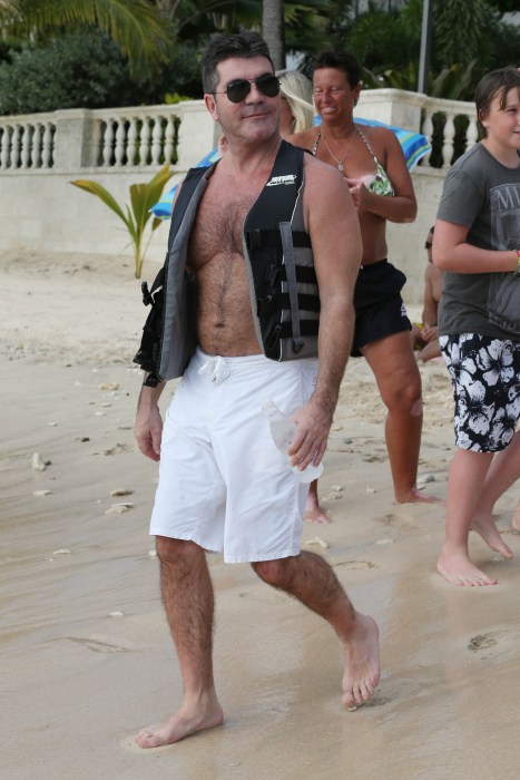 Simon Cowell poses with fans before taking out a jet ski in the Caribbean.