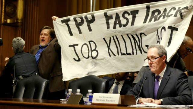 "A policewoman removes a man protesting the Trans-Pacific Partnership (TPP) as U.S. Trade Representative Michael Froman (R) testifies before a Senate Finance Committee hearing on ""President Obama's 2015 Trade Policy Agenda"" on Capitol Hill in Washington January 27, 2015. The top U.S. trade official urged Congress to back the administration's trade agenda on Tuesday and said an ambitious Pacific trade pact is nearing completion. Froman said the administration looked to lawmakers to pass bipartisan legislation allowing a streamlined approval process for trade deals, such as the 12-nation Trans-Pacific Partnership. REUTERS/Kevin Lamarque (UNITED STATES - Tags: POLITICS BUSINESS CIVIL UNREST)"