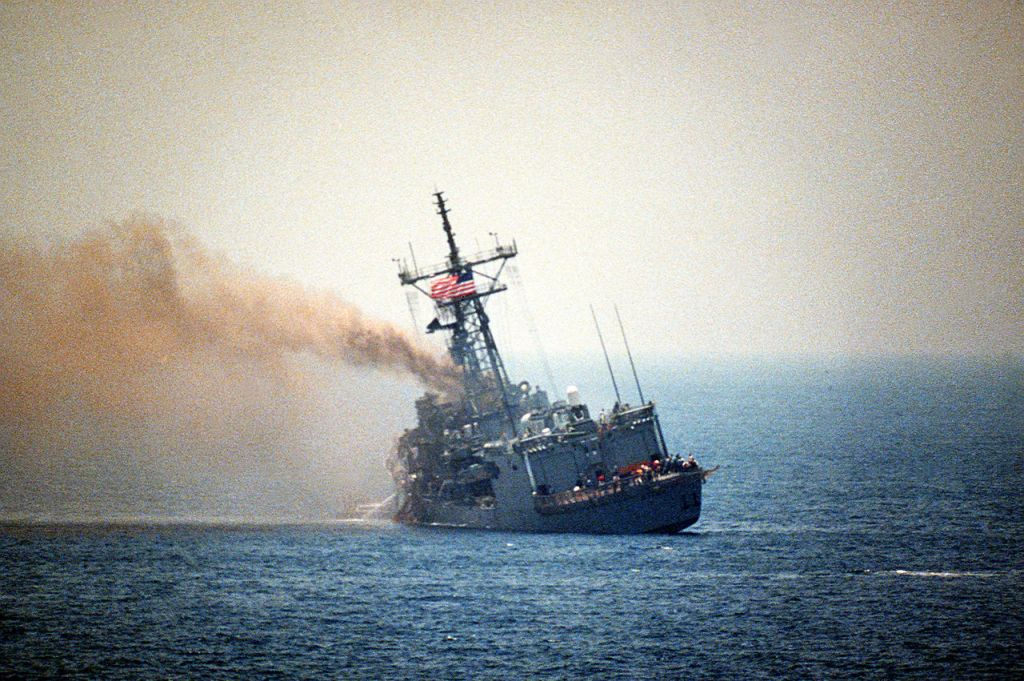 The USS Stark (FFG 31) burns and lists to port on 18 May 1987, one day after the guided missile frigate was struck by two Iraqi-launched Exocet missiles. The attack killed 37 sailors.